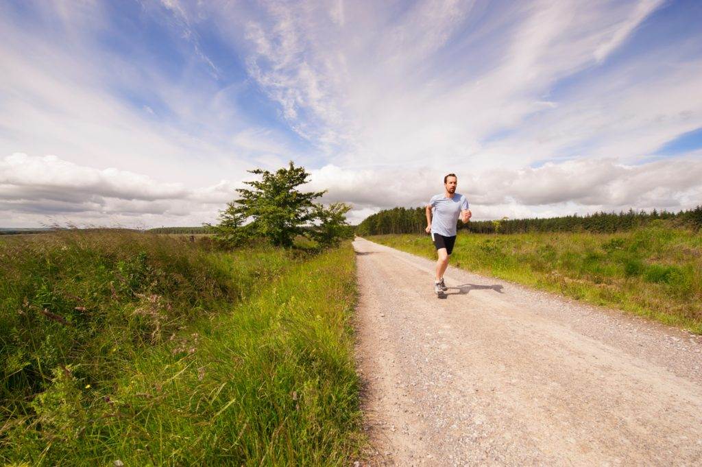 man-running-down-country-road