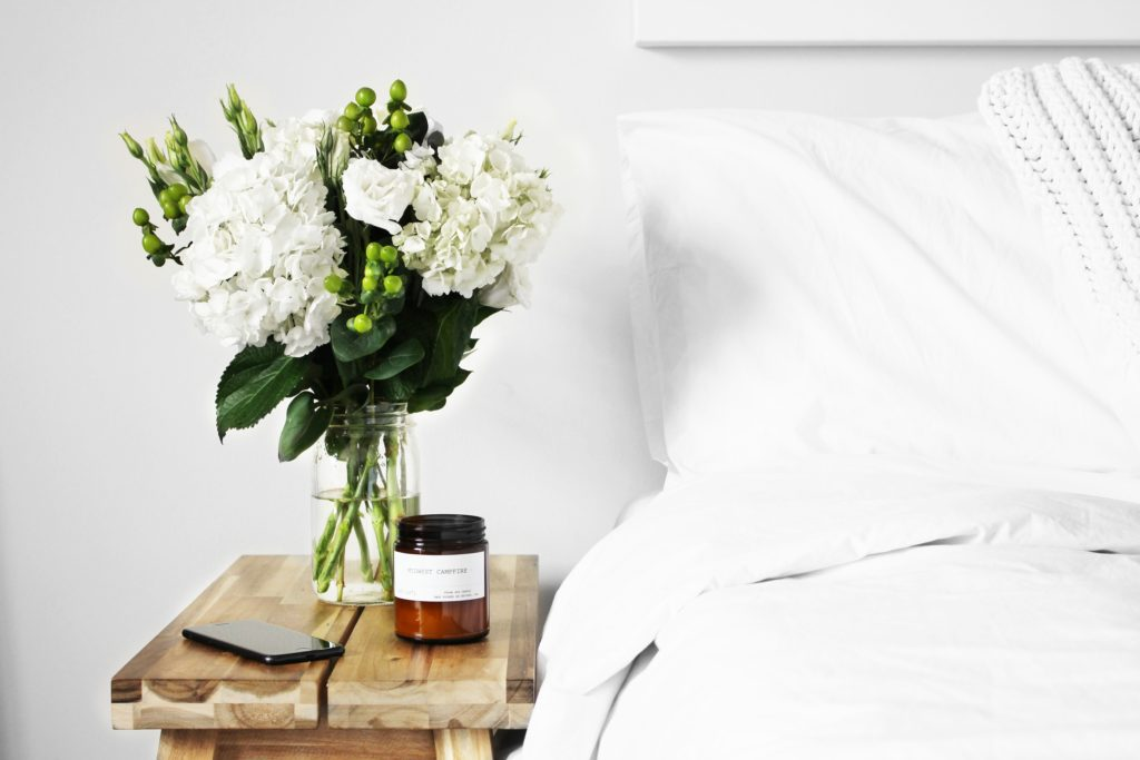 flowers-on-a-wooden-bedside-table-next-to-white-bed