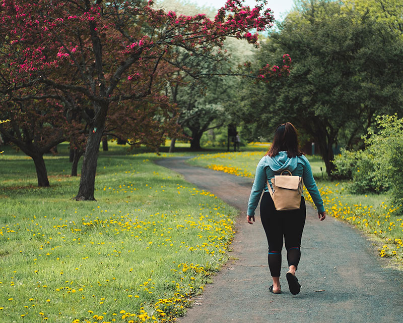 woman-walking-on-paved-trail-at-park
